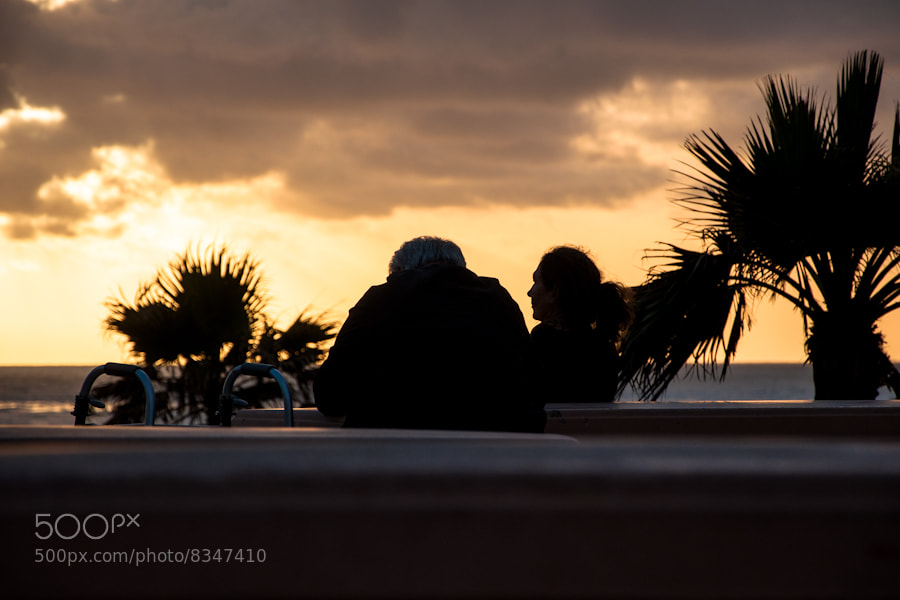 elderly gentleman and woman, watching the sunset, solana beach, california