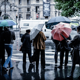 Umbrellas and wet streets outside Galeries Lafayette in Paris, France
