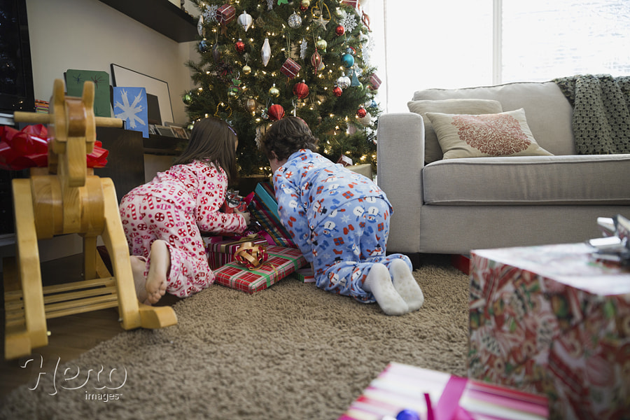 Siblings searching through Christmas gifts at home by Hero Images  on 500px.com