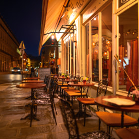 Empty tables at Le Petit Mâchon as night falls over the streets of Paris, France