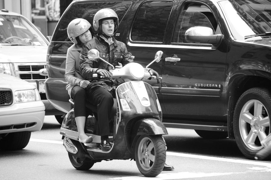 Couple riding a vespa at the stop light on 5th and 48th headed south.