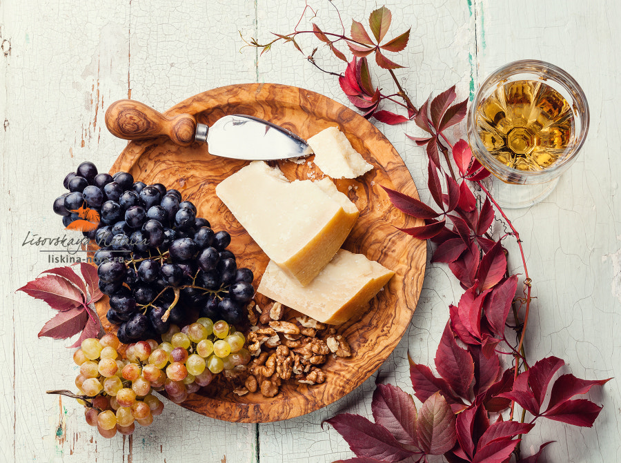 Parmesan cheese and grapes on olive wood plate and wine