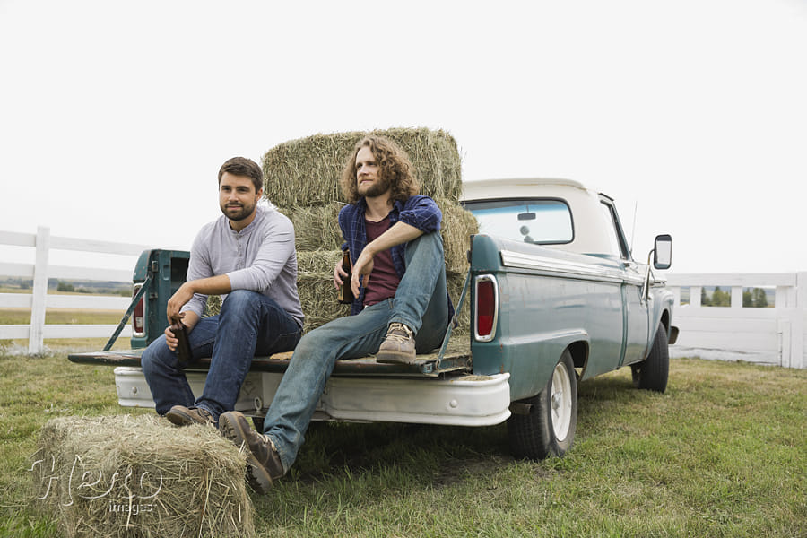 Friends sitting against hay bales in back of pick-up truck