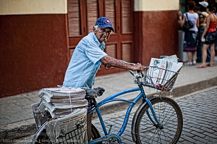 How the Cuban Newspaper, Granma, is delivered daily.  The Cubans in the background are waiting in line for the store.