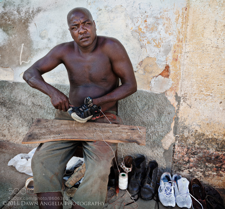 """The Shoeman."" In Trinidad, Cuba I met this fellow. He was the local town's shoe repair man. There laid a line of shoes, awaiting his touch. Most Cubans I spoke to only had a couple pair of shoes. Often brought to them by family members or tourists. My friend here was hard at work, but gave me a moment of his time, as all Cubans I encountered did. The sense of familiarity and brotherhood resides high in the Cuban people."