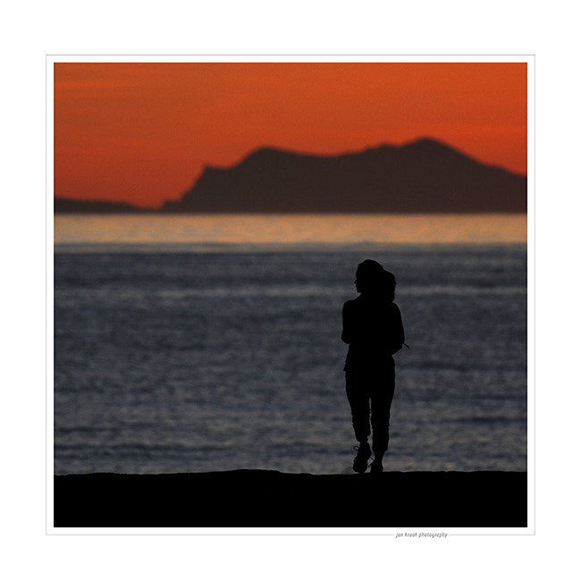 A woman goes for an early evening run at the beach in Malibu (California).