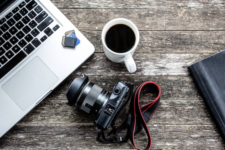 Laptop with digital camera and a coffee cup. by Benjamin King on 500px.com