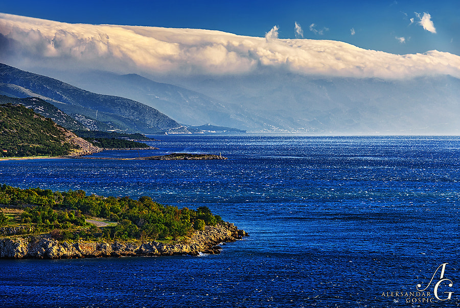 Bura wind along the North Adriatic coast near Novi Vinodolski, in the background rises the wall of Velebit with a Bura wind cap, with Nehaj fortress in Senj town, near the coast