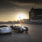 Постер, плакат: Gorgeous sunrise over the Nurburgring with Shelby Cobra and Porsche 550 Spider