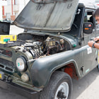 Постер, плакат: Man repairing an old Russian Jeep in Cuba streets
