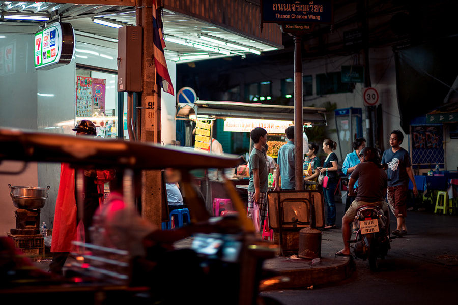 Night life on a Bangkok street corner in front of a 7-Eleven convenience store