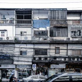 Street-level view of storefronts and apartments in Bangkok, Thailand