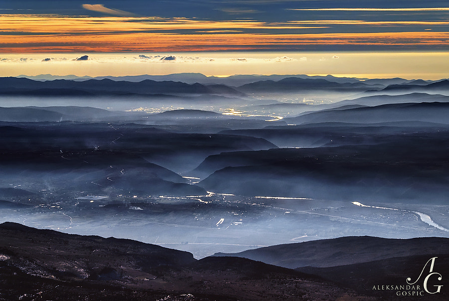 View from Velež mountain into a depth of 1800m towards the Neretva river valley, shrouded in a mystical veil of winter mist, and the last leg of her journey from Bosnia and Herzegovina to Croatia and the Adriatic Sea, which shines golden in the distance behind the Pelješac peninsula