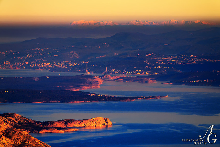 Morning on North Velebit. Rising sun spilled the color all over the Kvarner Bay, island of Krk, Krk island bridge, Rijeka city, and 215 km distant western Julian Alps, or groups of Kanin (2587m) in Slovenia and Jof Montasio (2752m) in Italy, which are peering above the layer of autumn mist