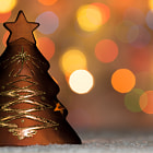 Постер, плакат: Xmas tree shaped candle holder standing in snow with christmas tree lights bokeh background and co