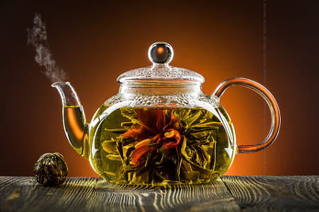 Glass teapot with blooming tea flower on wooden table by Kimberly Potvin on 500px