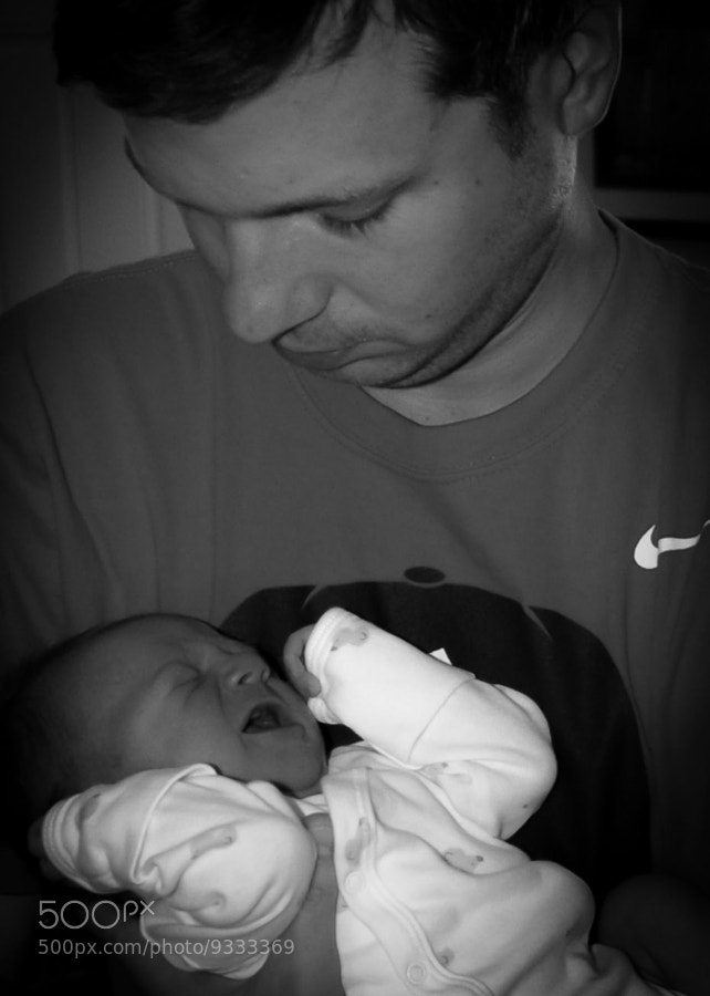A calm, confident, fatherly strength comforts an agitated newborn.