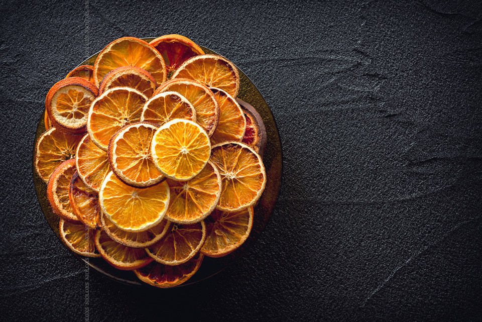 Dried oranges on black stone background