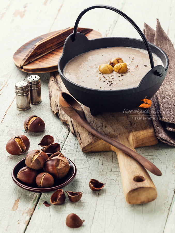 Chestnut soup in black iron pot with roasted chestnuts