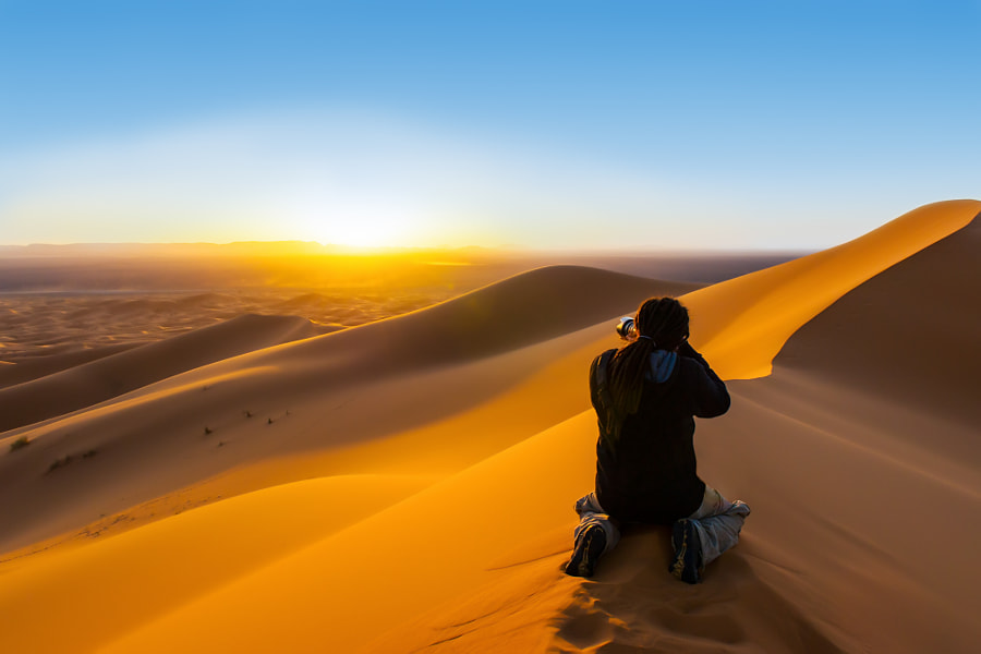 Handsome man with dreadlocks taking a photograph of sunset from a sand dune by Andrea Obzerova on 500px.com