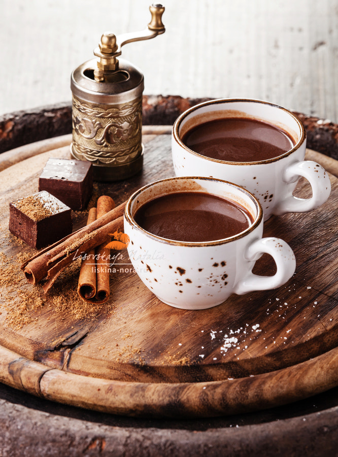 Hot chocolate sprinkled with white chocolate and spices on dark wooden background
