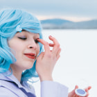 Постер, плакат: Young woman in blue wig and purple plastic coat applying purple makeup outdoors in the winter