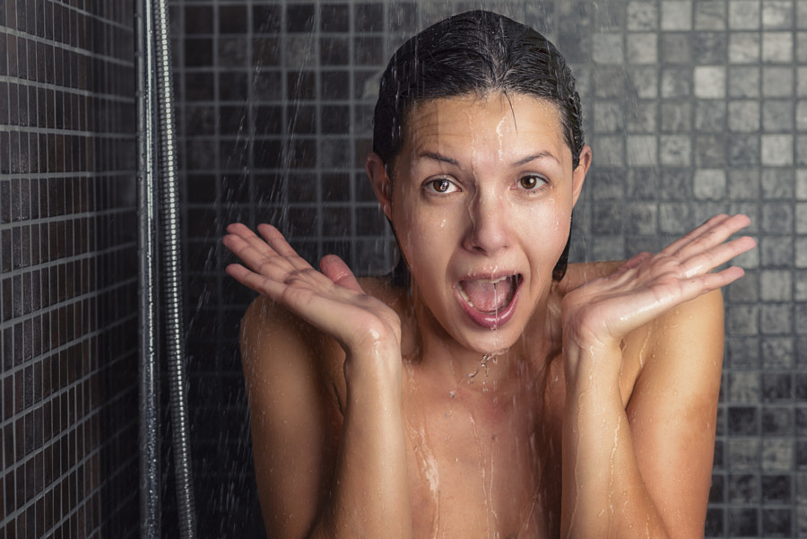 Young woman reacting in shock to hot shower water by Lars Zahner on 500px.com