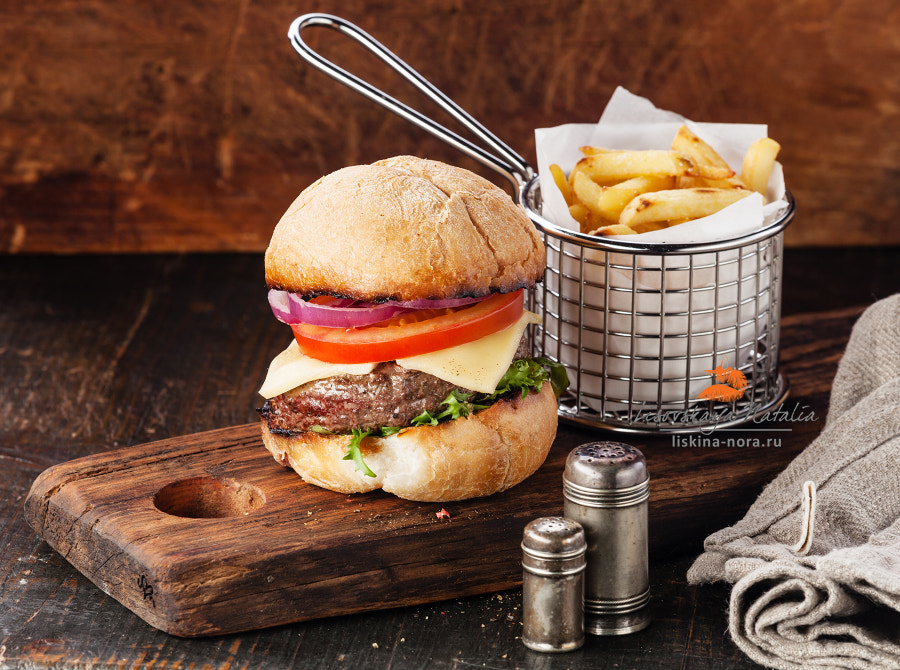 Burger with meat and French fries in basket