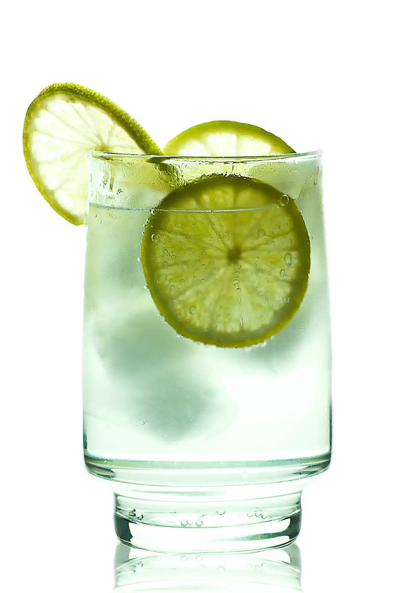 Photograph Glass of gin and tonic with ice cubes and lime slices by Gert Lavsen on 500px