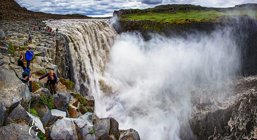 Over the most powerful waterfall in Europe, Detiffoss, the second longest river of Iceland, Jökulsá á Fjöllum, crashes thunderously in its canyon Jökulsárgljúfur. People on the other side of the canyon give the true measure of grandeur.