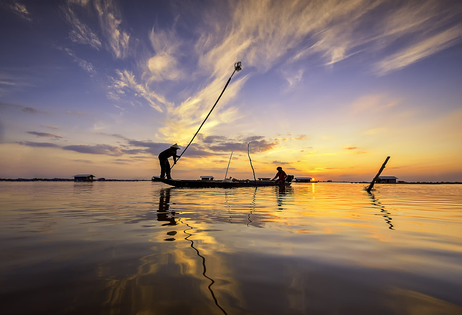 silhouette of fishermen with yellow and orange sun in the background by Extra suriyachat on 500px.com