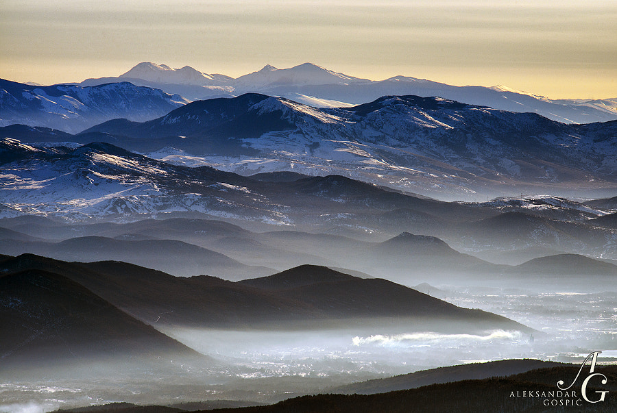 Mountains and valleys of Lika, filled with morning mist, viewed from Velebit mountain. In the middle is Poštak (1425m) mountain, while last at the back is Šator (1874m) mountain in Bosnia Herzegovina